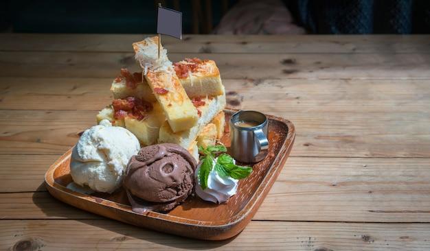Köstliches selbst gemachtes geröstetes brot, das mit vanille- und schokoladeneis und -peitschen dient