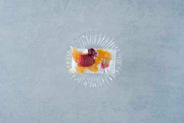 Köstliches stück kuchen auf glasplatte auf marmorhintergrund