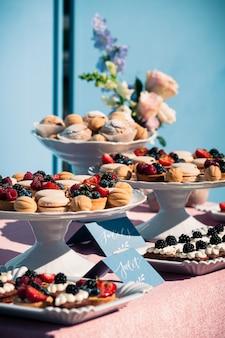 Köstliches süßes buffet mit kleinen kuchen, makronen, anderen nachtischen, blaues design