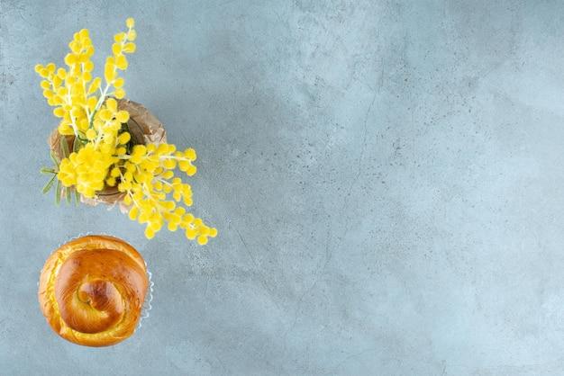 Köstliches süßes gebäck und gelbe blumen auf marmor.