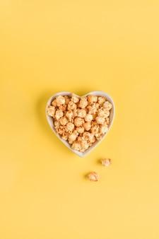Köstliches süßes popcorn mit karamell in der weißen keramikherzplatte, lokalisiert auf gelber tabelle der trendfarbe.