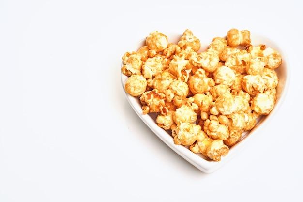 Köstliches süßes popcorn mit karamell in der weißen keramikherzplatte, lokalisiert auf weißem tisch.