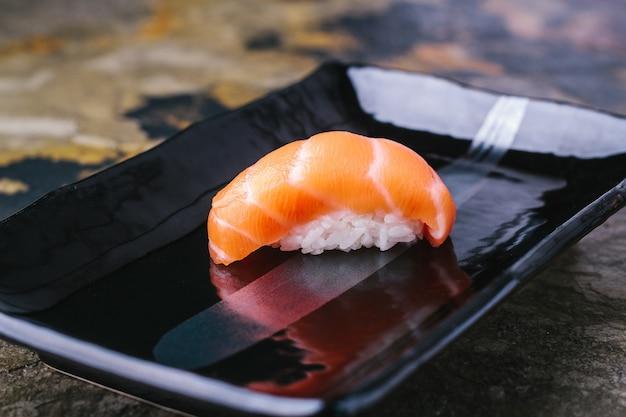 Köstliches sushi nigiri mit lachssake auf schwarzem teller traditionelle japanische küche