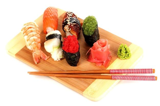 Köstliches sushi serviert auf holzbrett lokalisiert auf weiß