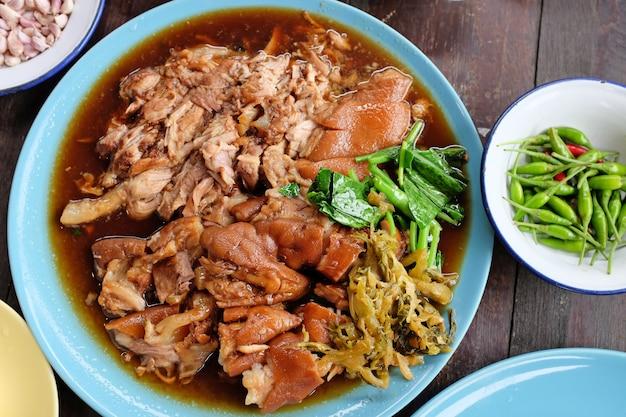 Köstliches thailändisches art-schweinefleisch-bein-eintopfgericht auf hölzerner tabelle. ansicht von oben.