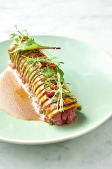 Köstliches thunfisch-tartar mit avocado, koriander, serviert auf roggencroutons in einem weißen teller mit pochiertem ei. snack der japanischen küche