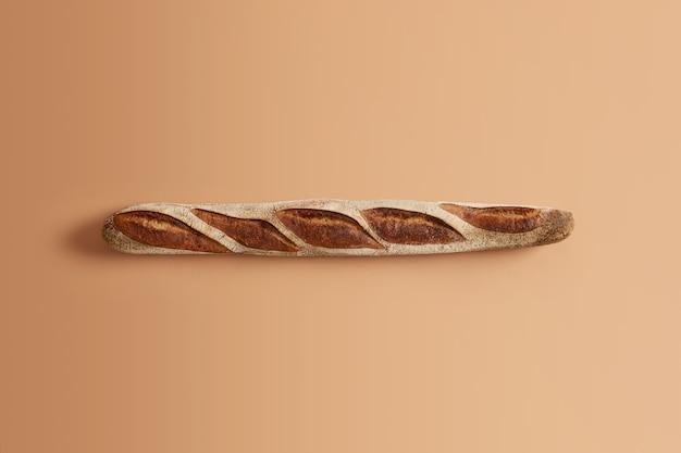 Köstliches traditionelles französisches knuspriges baguette, das von professionell gebacken wird, bereit, verbraucht zu werden, lokalisiert auf beigem hintergrund. bio-sauerteigprodukt. hausmannskost, bäckerei, naturkostkonzept.