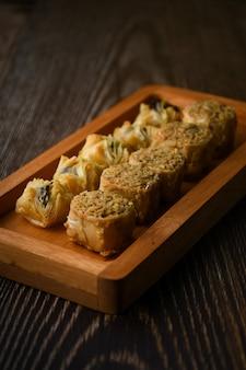 Köstliches türkisches baklava-süßgebäck mit honig auf holztablett