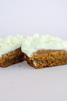 Köstliches und appetitliches stück kuchen mit sahne auf weißem hintergrund
