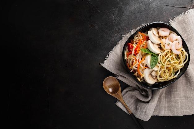 Köstliches und gesundes asiatisches essen auf einem schwarzen strukturierten hintergrund mit kopienraum