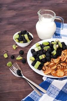 Köstliches und gesundes dessert aus mini-pfannkuchen, brombeeren und kiwi-beeren auf einem teller, zwei gabeln und einem krug milch auf einem holztisch.