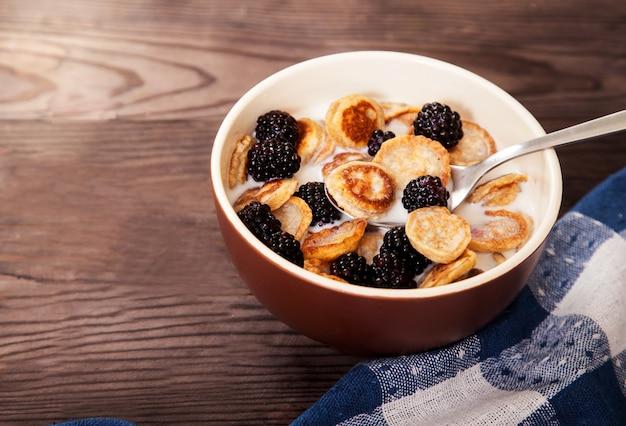 Köstliches und gesundes dessert von mini-pfannkuchen und brombeeren mit milch in einer keramikschale auf einem holztisch.