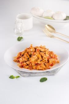 Köstliches und gesundes indonesisches essen in weißer platte mit goldener gabel und löffel auf weißem hintergrund