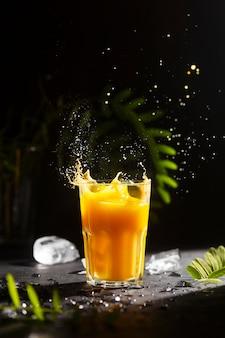 Köstliches und saures zitrusgetränk mit spritzern und tropfen auf einem tisch mit eis und grünen pflanzenblättern