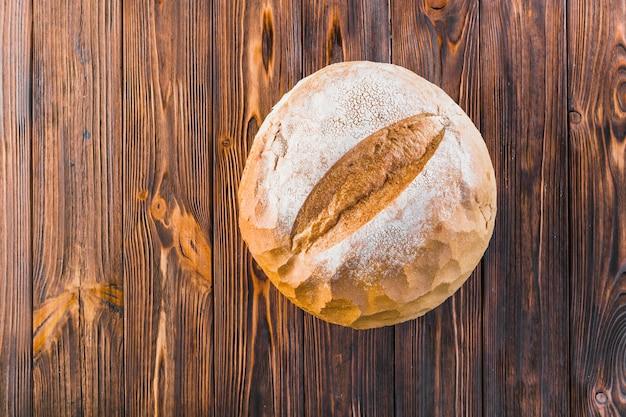 Köstliches vollständiges rundes brot auf hölzernem hintergrund