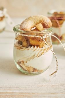 Köstliches weihnachtsplätzchen-dessert mit bratapfel und sahne auf einem holzteller auf einem weißen tisch