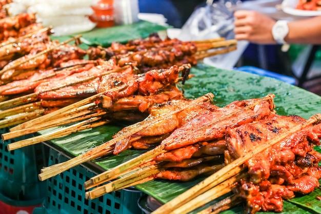 Köstliches würziges gegrilltes hühnerfleisch auf stöcken, thailändisches lebensmittel