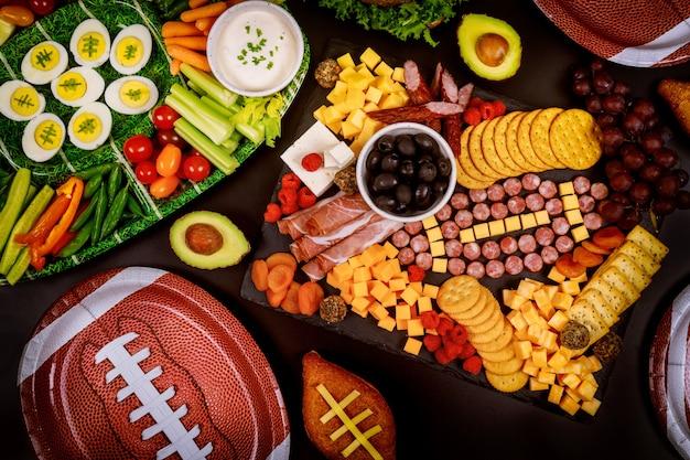 Köstliches wurstbrett und gemüse mit eintauchen zum anschauen des american-football-spiels.