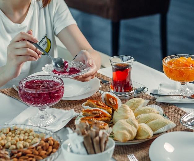 Köstlichkeiten und schwarzer tee auf dem tisch