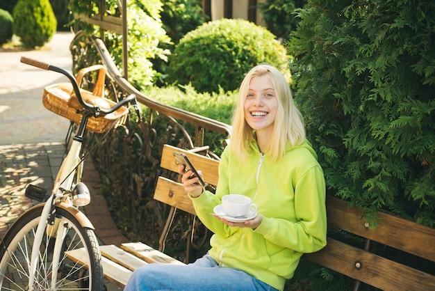 Koffein und energie. frau mit fahrrad im blühenden garten. wochenendaktivität. aktive freizeit und lifestyle. mädchen fahren zum spaß fahrrad. blonde genießen im park oder garten entspannen. aktives mädchen mit fahrrad.