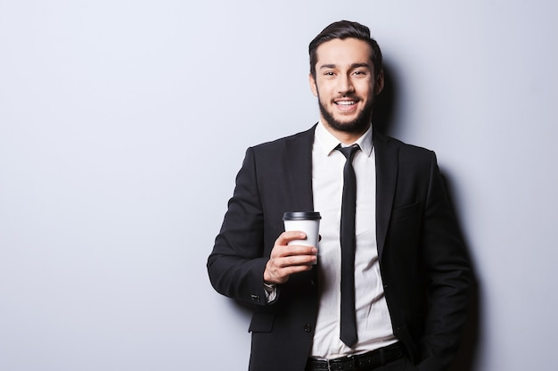 Koffein zum aufladen vor der arbeit. porträt eines selbstbewussten jungen mannes in formeller kleidung, der die kamera anschaut und eine tasse kaffee hält, während er vor grauem hintergrund steht