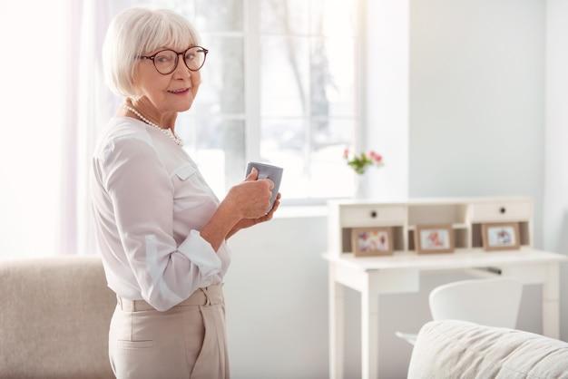 Koffeinliebhaber. angenehme hübsche ältere frau, die halb gedreht im wohnzimmer steht und posiert, während eine tasse kaffee hält