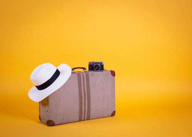 Koffer fotokamera hut, gelber hintergrund, reisekonzept