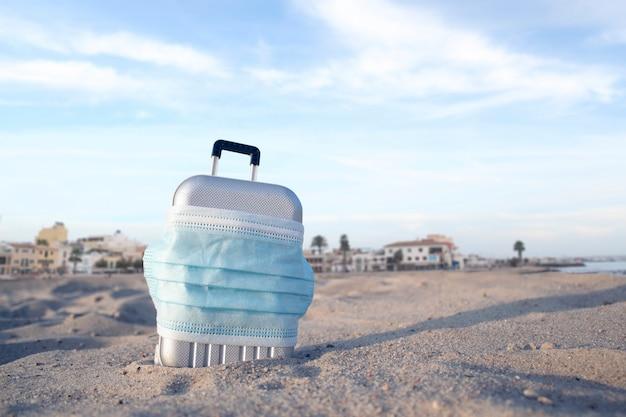 Koffer für die reise mit einer medizinischen maske am strand