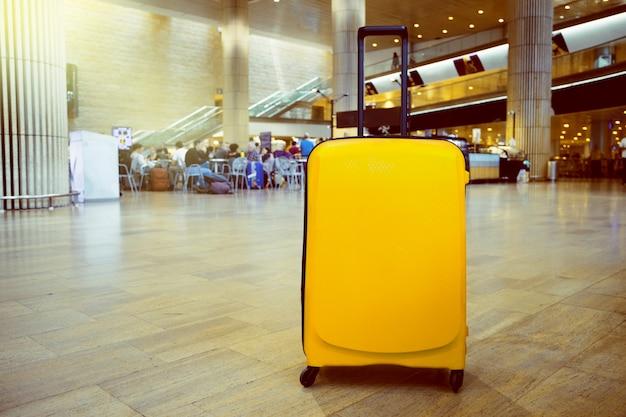 Koffer im wartebereich des flughafenabfertigungsgebäudes mit aufenthaltsraumzone als hintergrund. urlaub thema konzept.