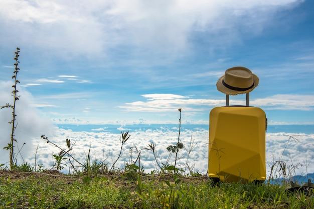 Koffer mit hut auf der landschaft mit seewolken