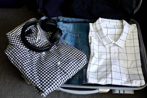 Koffer zu hause mit lässigen mannartikeln, sachen - jeans, hemden, kopfhörern im koffer für reisen, reisen, urlaub. speicherplatz kopieren.