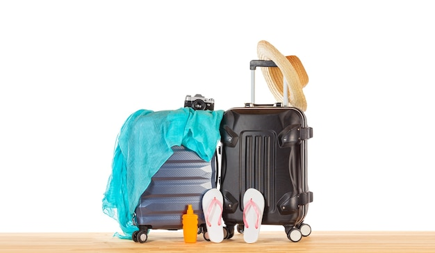 Koffergepäck mit strohhut, blauem pareo, flip flops, sonnenschutzflasche und retro-kamera