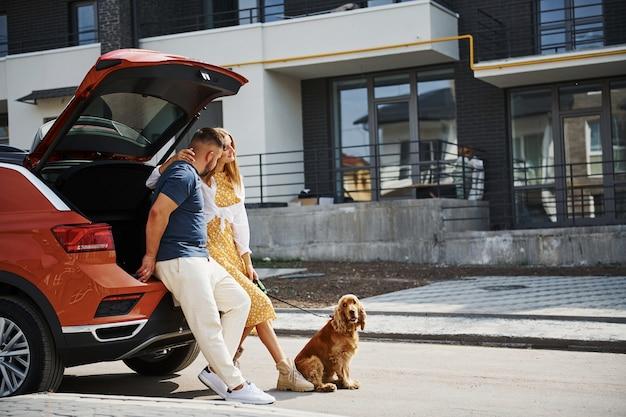 Kofferraum ist geöffnet. schönes paar geht zusammen mit hund draußen in der nähe des autos spazieren.