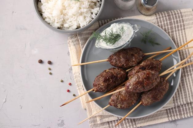 Kofta kebab auf holzspießen auf einem teller mit sauce und einer beilage reis