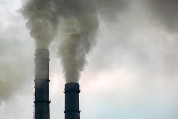 Kohlekraftwerk hohe rohre mit schwarzem rauch, der die umweltverschmutzende atmosphäre nach oben bewegt.