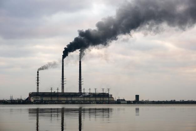 Kohlekraftwerk hohe rohre mit schwarzem rauch, der sich nach oben bewegt, verschmutzende atmosphäre mit reflexionen davon im seewasser.