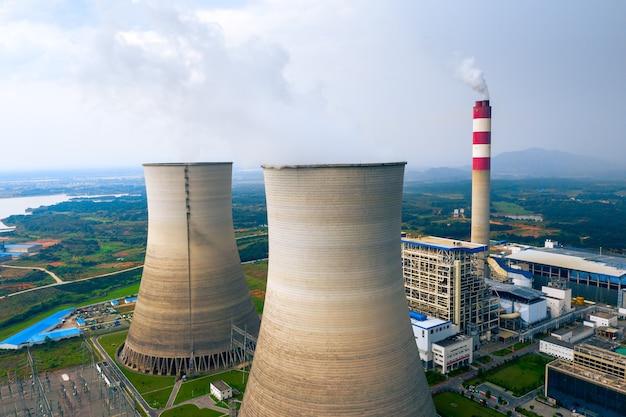 Kohlekraftwerk mit kühltürmen, die dampf in die atmosphäre abgeben