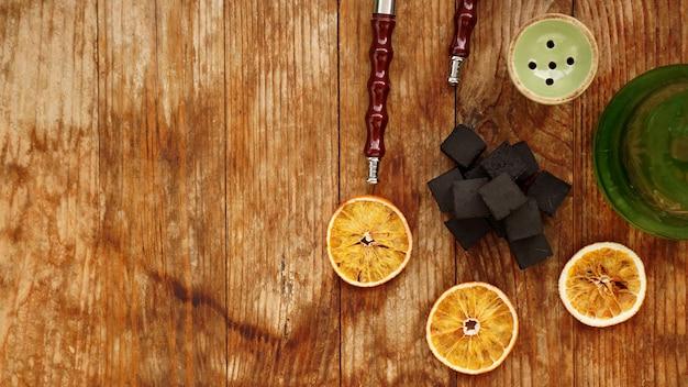 Kohlen für wasserpfeife auf hölzernem hintergrund mit trockenen orangen und schüssel. platz für text und draufsicht