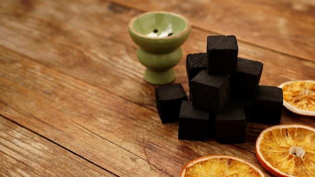 Kohlen für wasserpfeife auf hölzernem hintergrund mit trockenen orangen und schüssel. platz für text