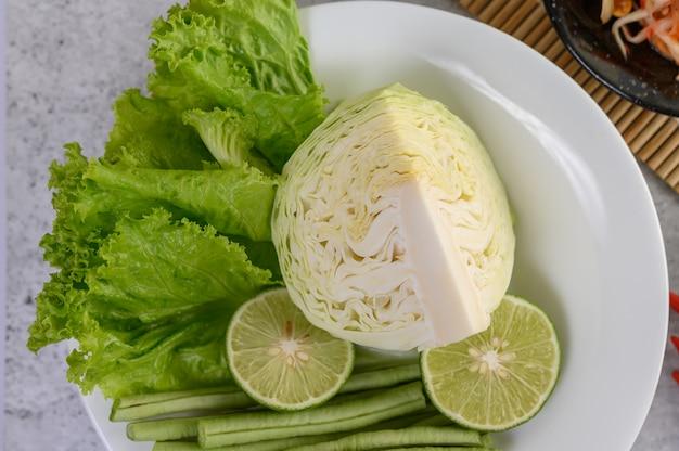 Kohlgrün, kalk, yard-lange bohnen und salat auf einer weißen platte