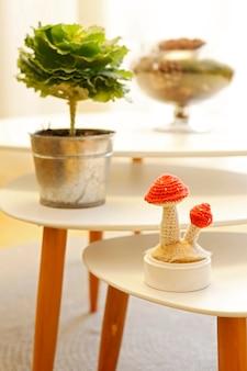Kohlpflanze in einem zinktopf und dekorativer handgemachter makramee-pilz auf einem kleinen tisch