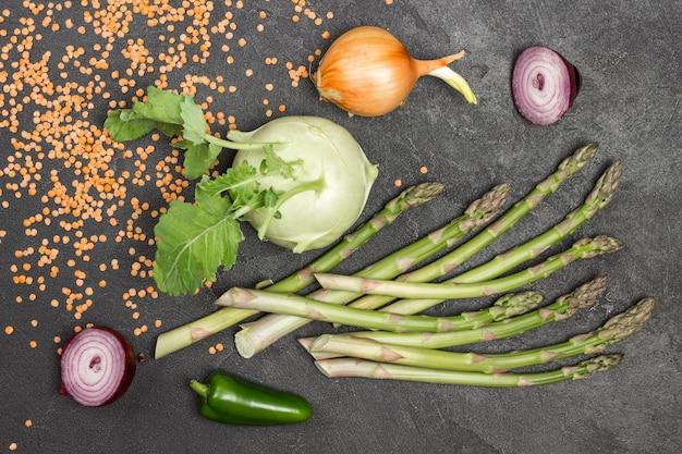 Kohlrabi und grüner spargel auf dem tisch. zwiebeln und linsen. schwarzer hintergrund. flach legen