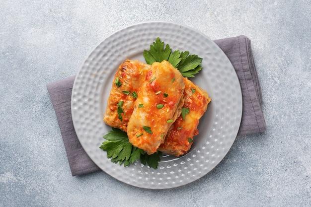 Kohlrouladen mit rindfleisch, reis und gemüse auf der platte. gefüllte kohlblätter mit fleisch. grauer konkreter tabelle kopienraum.