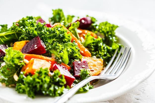 Kohlsalat mit gebackenem gemüse in der weißen platte.
