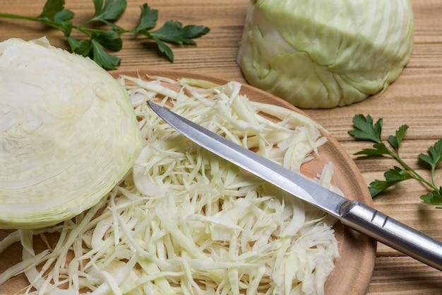 Kohlscheiben, messer auf schneidebrett, halber kohlkopf. frisches veganes essen. nahansicht
