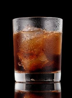 Kokagetränk in einem glas mit eisschwarzer oberfläche