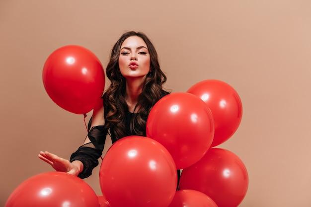 Kokette frau in der schwarzen bluse hält luftballons und bläst kuss auf beigem hintergrund.