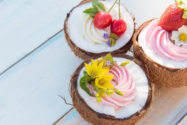 Kokos-cupcakes mit blumen, erdbeeren und käsecreme. draufsicht