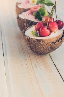 Kokos-cupcakes mit blumen, erdbeeren und käsecreme