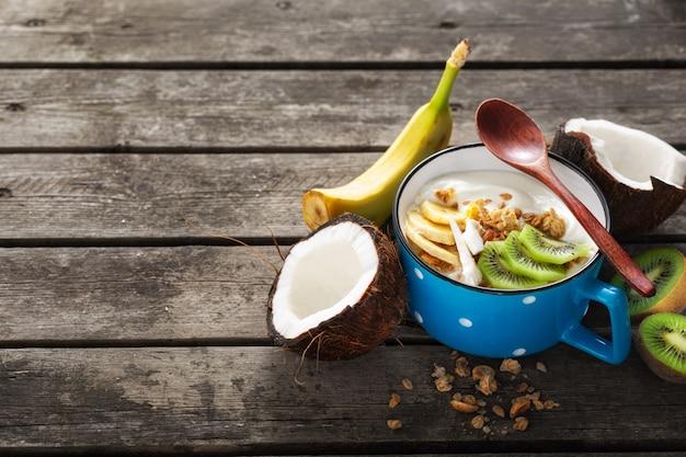 Kokos-joghurt-früchte mit müsli serviert auf holztisch. speicherplatz kopieren. probiotisches lebensmittelkonzept. leckeres und gesundes frühstück